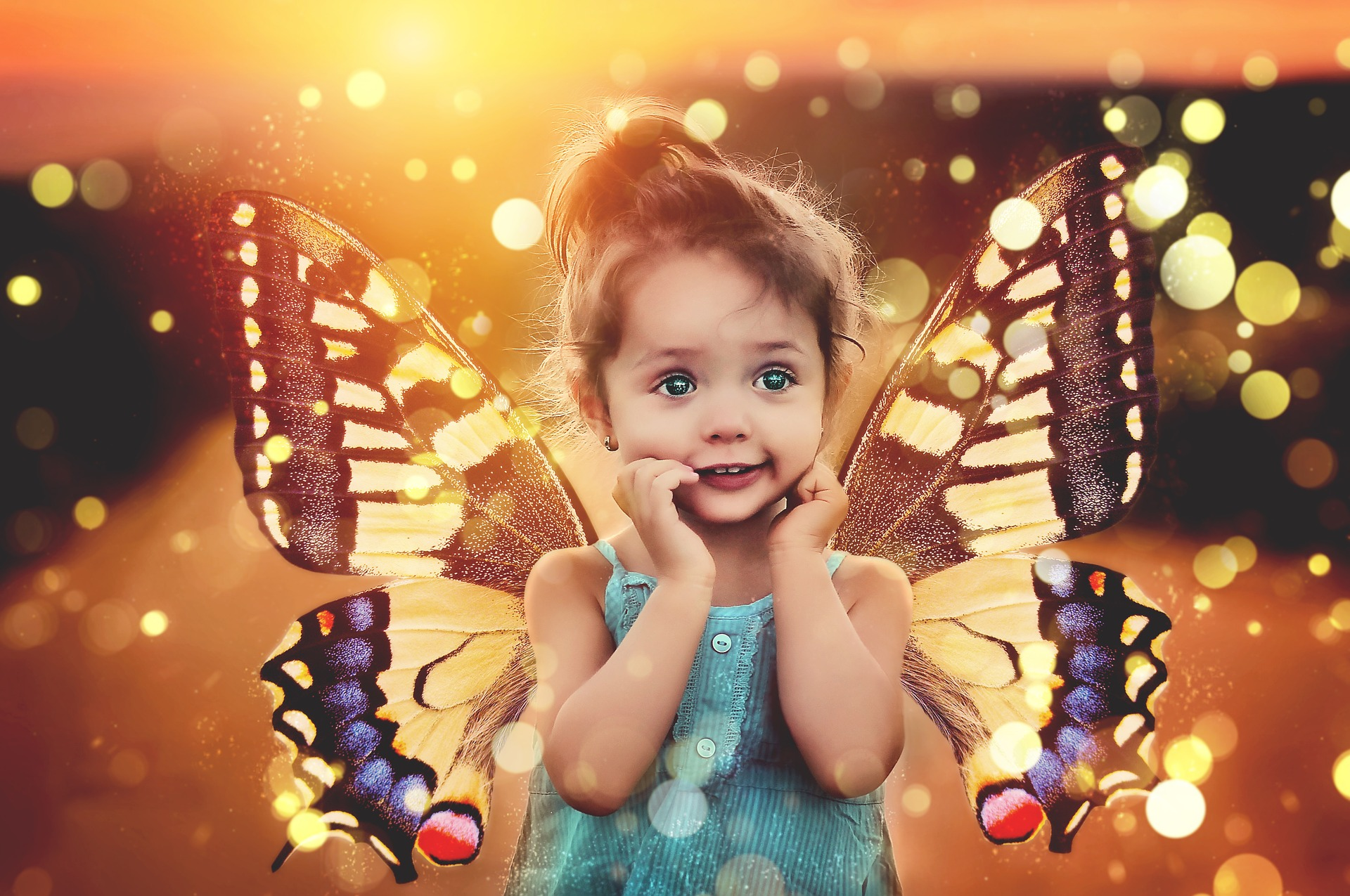 Photo of female child with hands pressed to chin, wearing butterfly wings